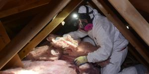 BPI Certified Professional adding batts of insulation to an attic