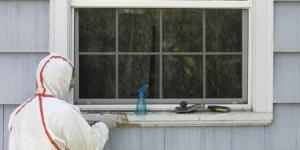 Man in full coverage hazard suit removing lead paint from windowsill